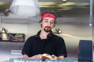 Young man slicing hamburger bread roll on fast food vanの写真素材 [FYI03553181]