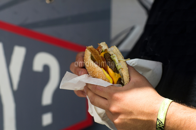 Male customer's hand eating hamburger from fast food vanの写真素材 [FYI03553183]