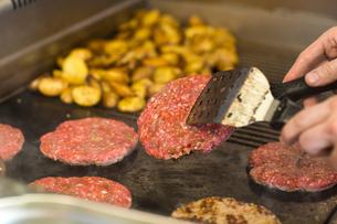 Man's hand frying burger on fast food vanの写真素材 [FYI03553184]