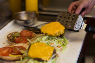 Man's hand preparing cheeseburger in fast food van kitchenの写真素材 [FYI03553189]