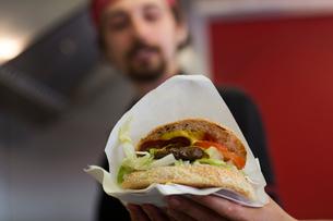 Young man serving hamburger from fast food vanの写真素材 [FYI03553191]