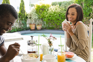 Young couple sharing eating breakfast together by swimming poolの写真素材 [FYI03553264]