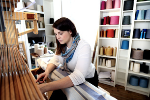 Young woman using loomの写真素材 [FYI03553285]