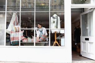 Shop owner arranging window displayの写真素材 [FYI03553286]