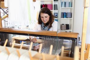 Young woman using loomの写真素材 [FYI03553289]