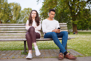 Young couple on park bench holding smartphoneの写真素材 [FYI03553329]
