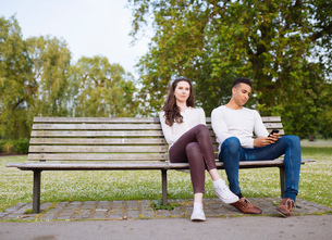 Young couple on park bench holding smartphoneの写真素材 [FYI03553330]