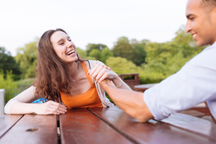 Young couple arm wrestling on picnic bench laughingの写真素材 [FYI03553335]