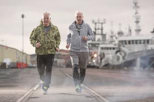 Front view of men jogging on docklandsの写真素材 [FYI03553397]
