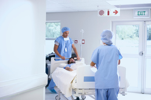 Doctors wearing surgical scrubs pushing patient on hospital bedの写真素材 [FYI03553410]