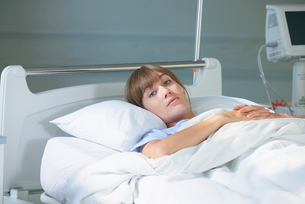 Woman lying on hospital bed looking at cameraの写真素材 [FYI03553423]