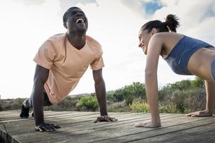 Couple doing push ups on wooden pathwayの写真素材 [FYI03553455]