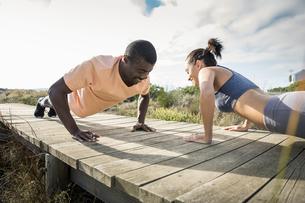 Couple doing push ups on wooden pathwayの写真素材 [FYI03553456]