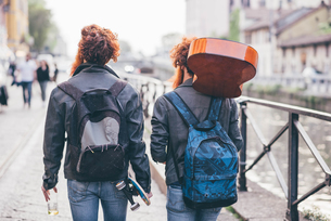 Rear view of young male hipster twins with red hair strolling along canal waterfrontの写真素材 [FYI03553568]