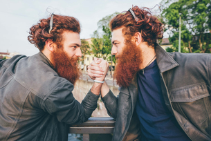 Young male hipster twins with red hair and beards arm wrestling on bridgeの写真素材 [FYI03553572]