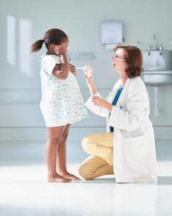 Girl listening to doctors stethoscope in hospital children's wardの写真素材 [FYI03553617]