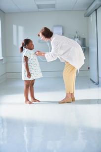 Female doctor using stethoscope on girl in hospital children's wardの写真素材 [FYI03553618]
