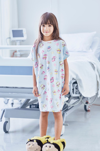 Portrait of girl patient wearing bumblebee slippers in hospital children's wardの写真素材 [FYI03553626]