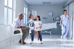 Male doctor talking to girl patient and her mother in hospital children's wardの写真素材 [FYI03553646]