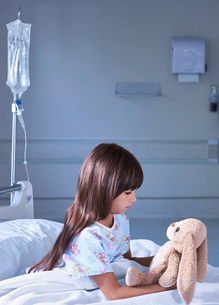 Girl patient gazing at toy rabbit on hospital children's wardの写真素材 [FYI03553659]