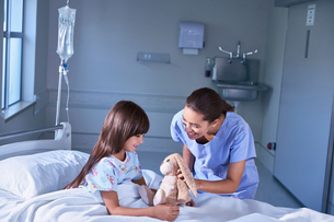 Nurse and girl patient playing with toy rabbit on hospital children's wardの写真素材 [FYI03553662]