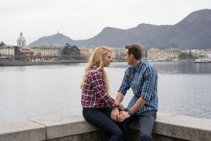 Romantic young couple holding hands on harbour wall, Lake Como, Italyの写真素材 [FYI03553731]