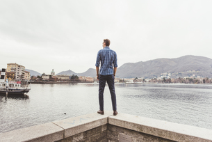 Rear view of young man standing on harbour wall looking out, Lake Como, Italyの写真素材 [FYI03553736]