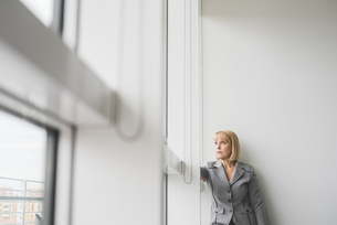 Mature businesswoman staring up through office windowの写真素材 [FYI03553767]