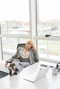 Bored mature businesswoman with feet up on office deskの写真素材 [FYI03553776]