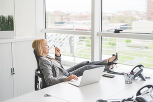 Mature businesswoman with feet up on office deskの写真素材 [FYI03553778]