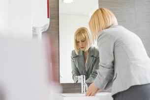 Mature businesswoman washing hands in office powder roomの写真素材 [FYI03553781]