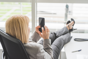 Mature businesswoman with feet up on office desk using smartphone touchscreenの写真素材 [FYI03553782]