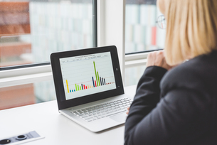 Over shoulder view of businesswoman looking at bar graph on office  laptopの写真素材 [FYI03553797]