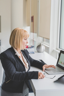 Mature businesswoman looking at bar graph on office  laptopの写真素材 [FYI03553800]