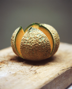 Cantaloupe melon sliced open on rustic wooden chopping boardの写真素材 [FYI03553808]