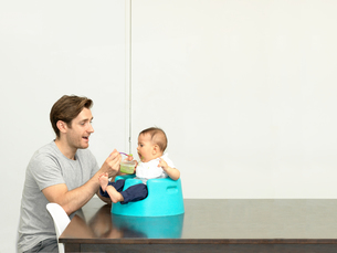 Father feeding baby boy in baby seatの写真素材 [FYI03553871]