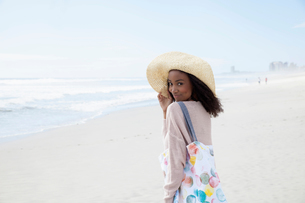 Young woman wearing hat on beachの写真素材 [FYI03554020]