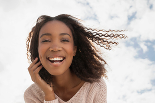 Happy young woman on windy dayの写真素材 [FYI03554025]