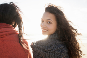 Young women wrapped in knitted shawl on cold windy dayの写真素材 [FYI03554044]