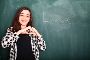 Girl gesturing heart shaped hands beside 'Love' word on blackboardの写真素材 [FYI03554052]