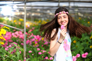 Happy girl in hothouse of pink flowersの写真素材 [FYI03554053]