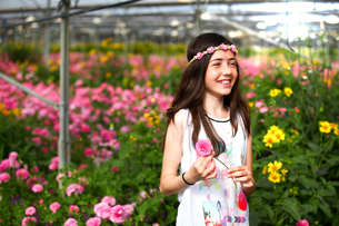 Happy girl in hothouse of pink flowersの写真素材 [FYI03554054]