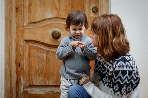 Mother and girl in front of wooden doorの写真素材 [FYI03554275]