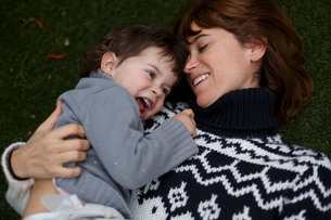 Girl lying on mothers chest smilingの写真素材 [FYI03554284]