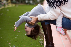 Girl sitting on mothers knee leaning backの写真素材 [FYI03554289]