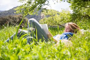 Woman lying on grass readingの写真素材 [FYI03554356]