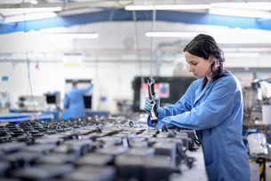 Female worker assembling components in circuit board assembly factoryの写真素材 [FYI03554370]