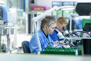 Female worker soldering component onto circuit boards in circuit board assembly factoryの写真素材 [FYI03554372]