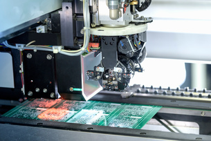 Robot placing components onto circuit board in circuit board assembly factoryの写真素材 [FYI03554375]