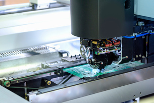 Robot placing components onto circuit board in circuit board assembly factoryの写真素材 [FYI03554376]